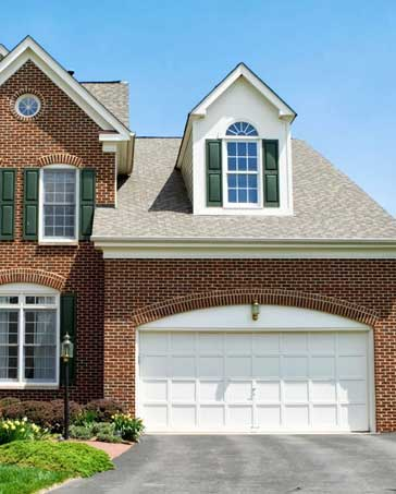 Brick-home-with-a-large-white-two-car-garage-door